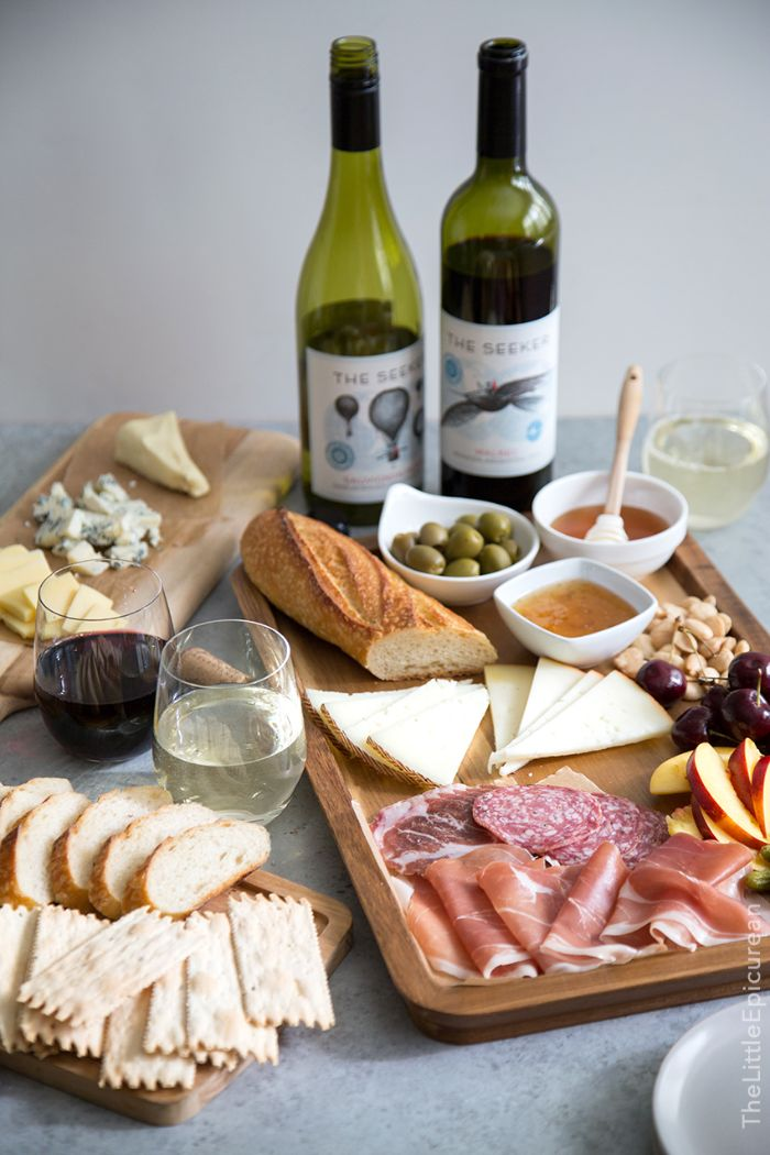 two wine glasses next to wooden board meat and cheese board baguette olives fruits and nuts
