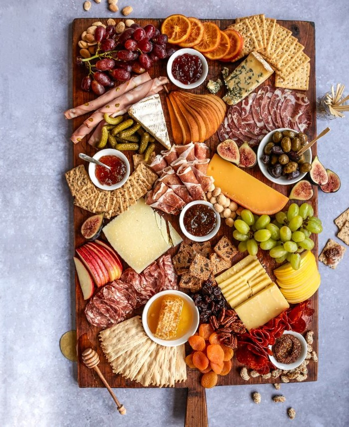 what is a charcuterie board wooden tray covered with types of cheese meat fruits condiments veggies