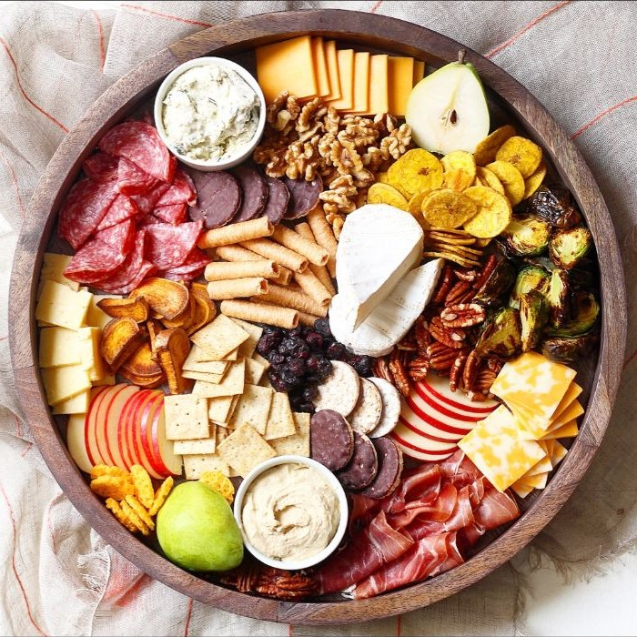 what is charcuterie round wooden tray filled with meats cheeses crackers nuts condiments in small bowls