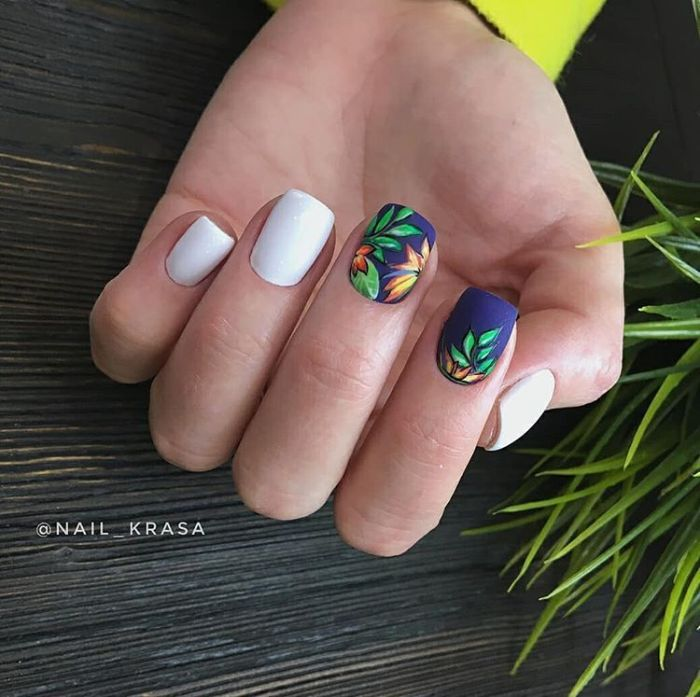 white and blue matte nail polish 2021 nail trends decorations of green leaves orange flowers on middle and index fingers