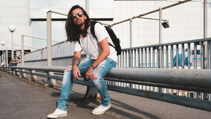 white t shirt with ripped jeans white converse sneakers worn by man with long black hair mens hip hop clothing