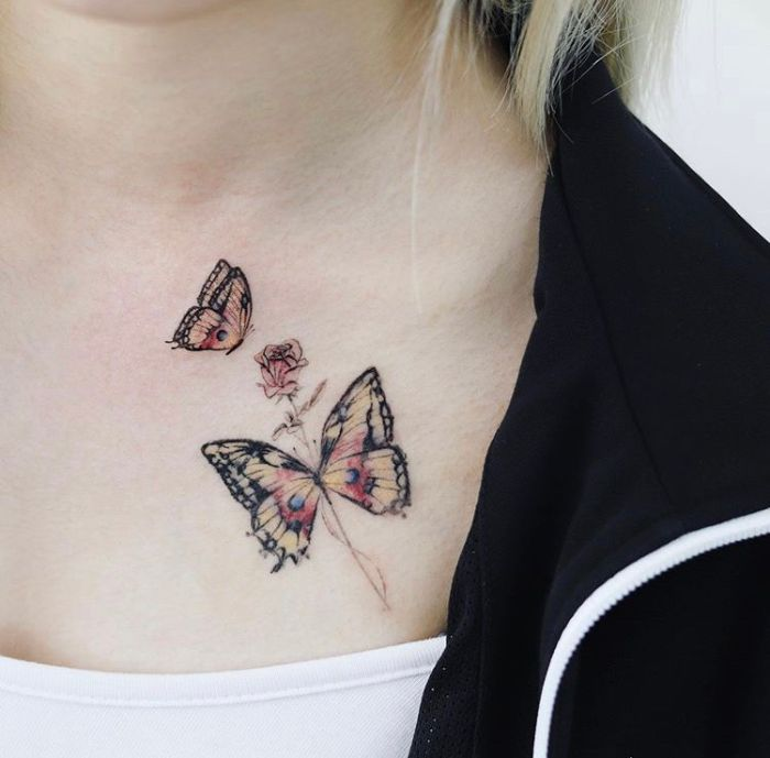 white top black hoodie small butterfly tattoo colored butterflies with a rose collarbone tattoo