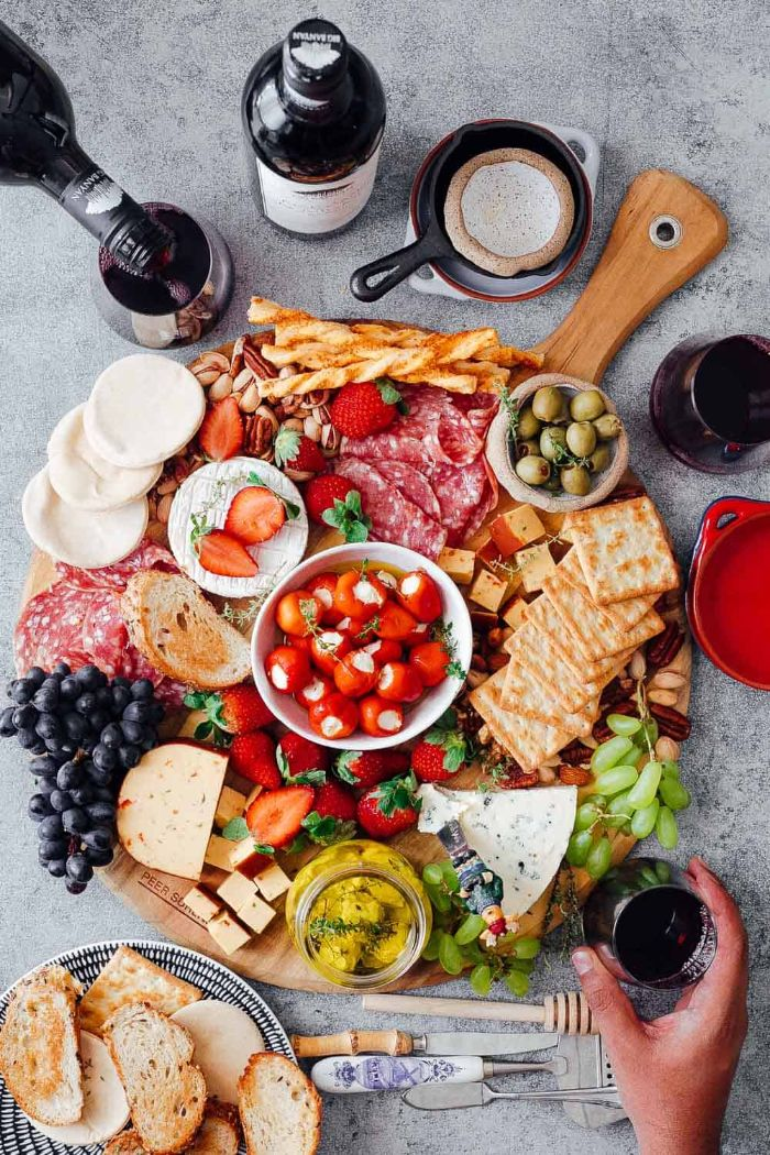 wine bottles and glass next to round wooden board meat and cheese platter with fruits veggies crackers nuts