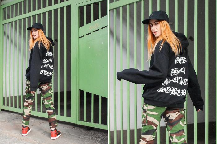 woman wearing black hoodie camouflage pants black hat streetwear fashion nike air jordan ones in black and red