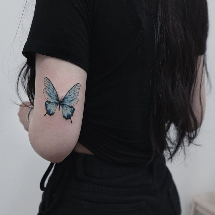woman wearing black jeans and t shirt butterfly tattoo meaning back of arm blue butterfly tattoo