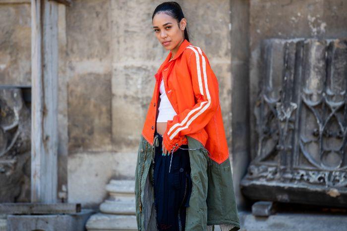 woman wearing orange and green oversized coat white top streetwear women standing on sidewalk