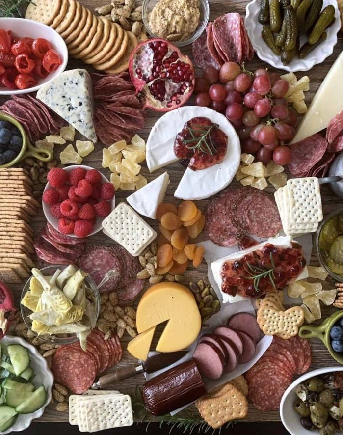 wooden board covered with fruits crackers meat and cheese platter condiments veggies