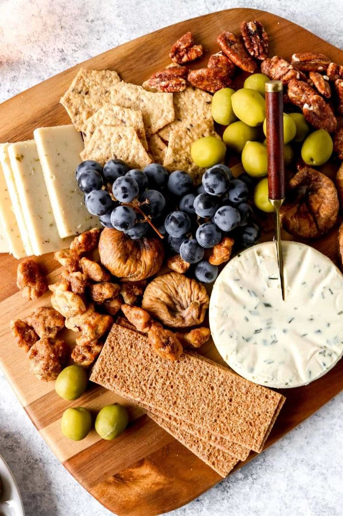 wooden board with cheeses crackers grapes dried fruit olives meat and cheese platter