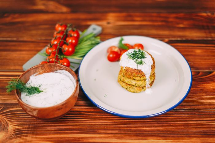 zucchini fritters arranged on white plate best appetizers to bring to a party yoghurt sauce on them with dill