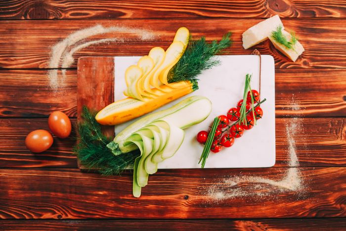 zucchini sliced placed on marble cutting board best appetizers to bring to a party wooden surface
