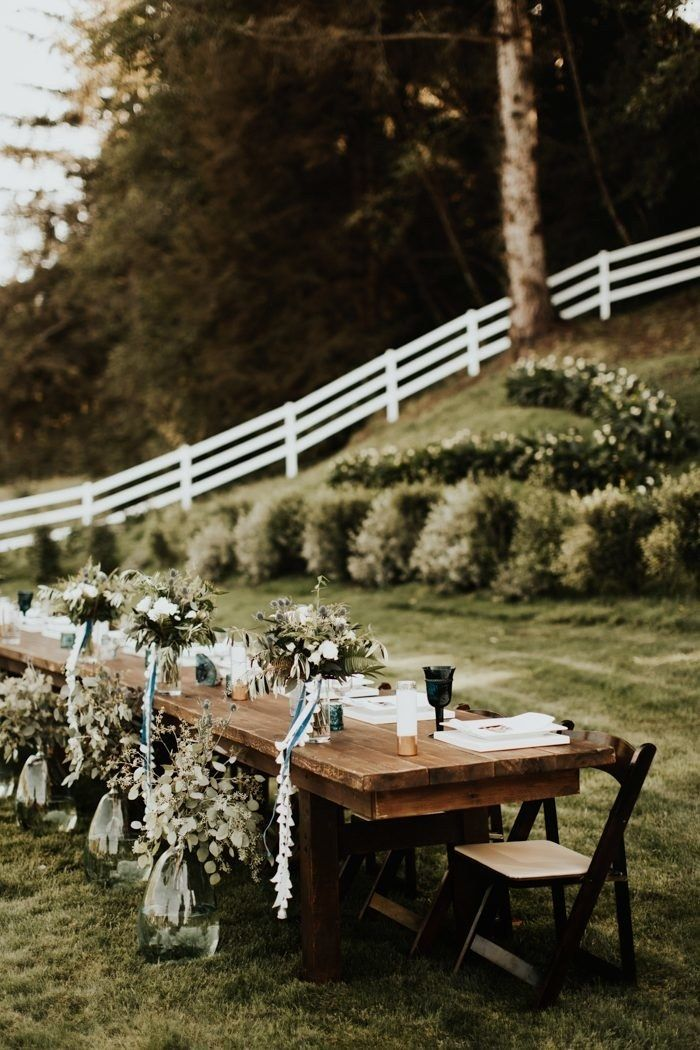 arrangements of flowers in front and on top of wood tablebackyard wedding placed on green grass field