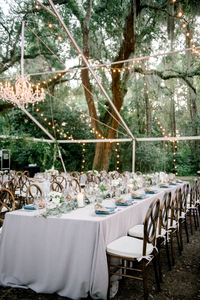 arrangements of flowers in the middle of long table with white table cloth rustic wedding ideas strings of lights hanging above