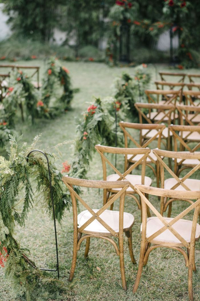 arrangements of garden flowers along the pathway backyard wedding chairs on both sides