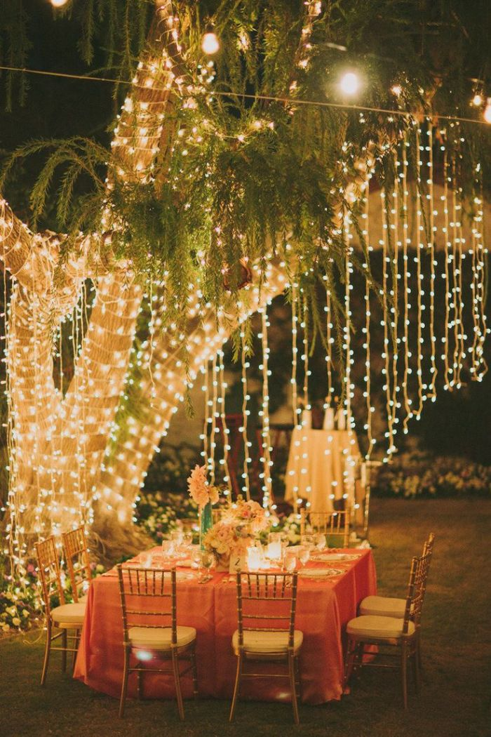 backyard wedding decorations tree wrapped with strings of lights table underneath with floral centerpiece