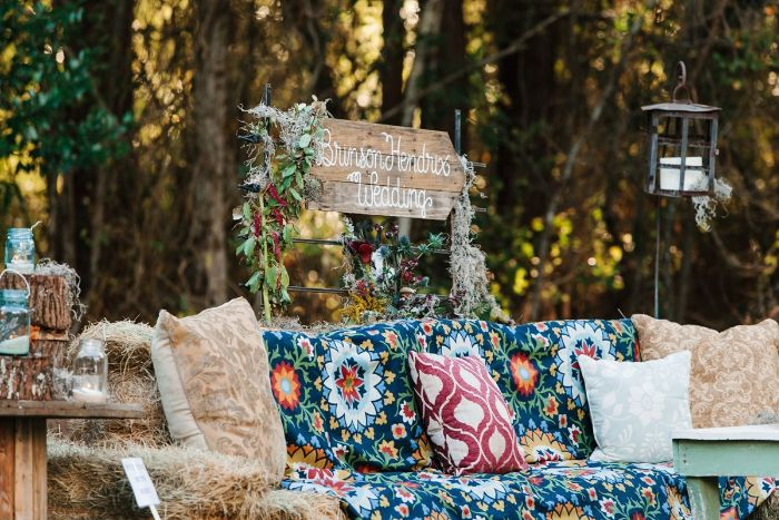 backyard wedding lounge space for photos made of hay with colorful blanket and throw pillows