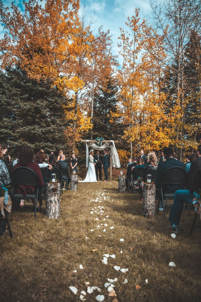 backyard wedding reception wood arch with flowers bride and groom in front of it white rose petals along the aisle