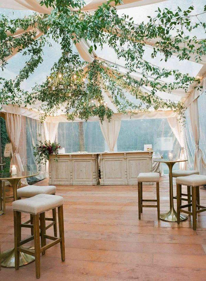 bar stools next to high tables under tent made of white curtains outdoor wedding decorations greenery hanging from the top