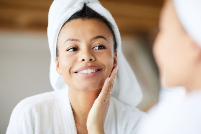 black haired woman wearing white bath robe and towel on her head hydrating face mask looking at a mirror