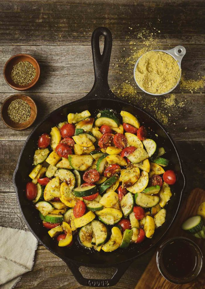 black skillet filled with sautéed squash zucchini and cherry tomatoes squash recipes garnished with parmesan
