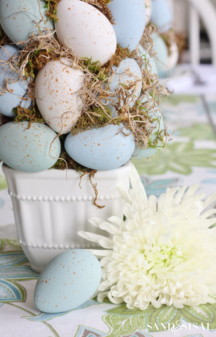 blue and white eggs with moss diy tree topiary easter decorations 2021 white flower next to it