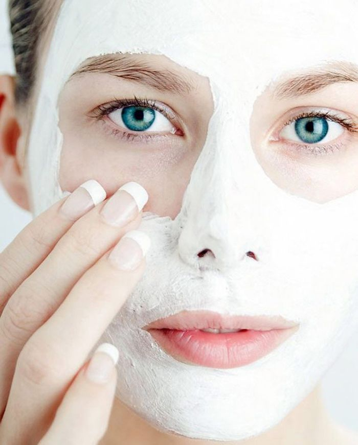 blue eyed woman putting on white face mask diy face mask for acne french manicure on her nails