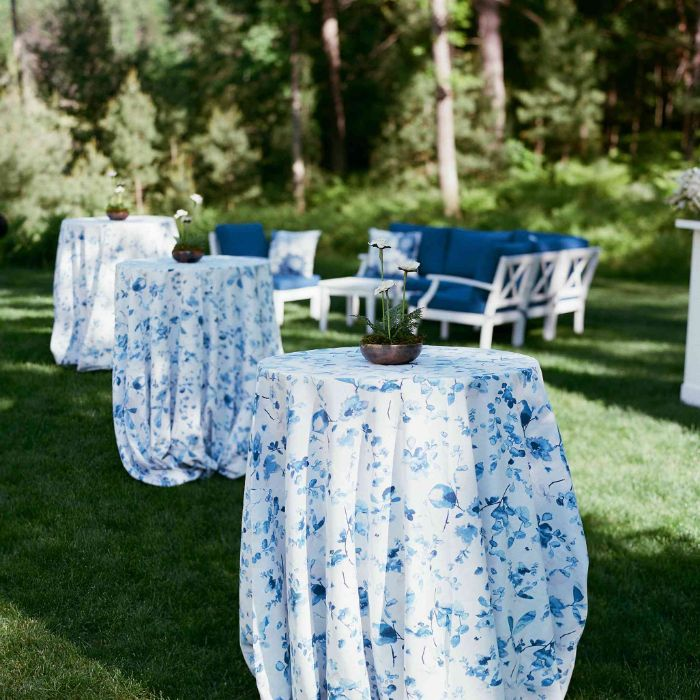 blue table cloths on tall tables with spring flowers in the middle rustic wedding ideas blue sofas in the background