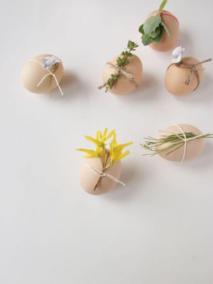 boiled eggs with different flowers tied to them with a strand or bakers twine easy easter crafts white background