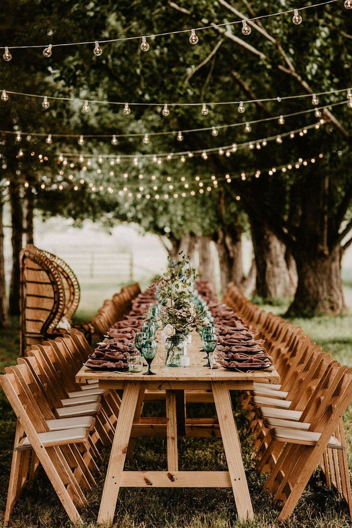 bouquets of spring flowers in the middle of long table surrounded by chairs backyard wedding ideas strings of lights hanging above