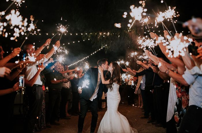 bride and groom kissing backyard wedding decorations people standing around them holding sparklers