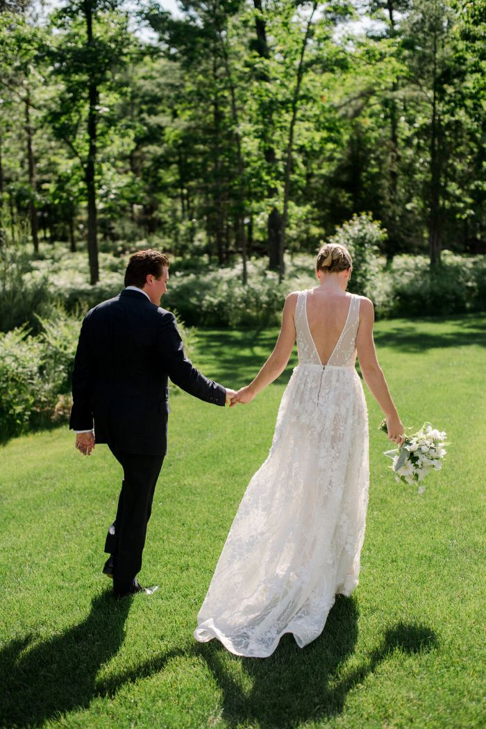 bride and groom walking on green grass field home wedding ideas lots of trees in the background