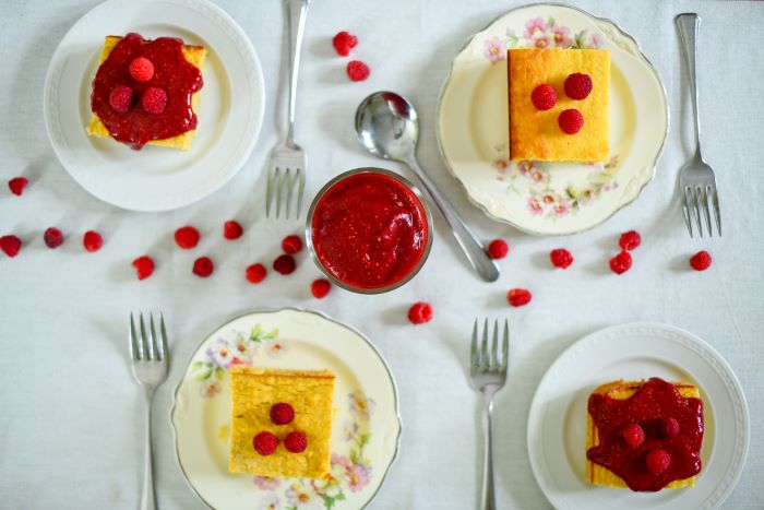 cake slices in four different plates zucchini and squash recipes garnished with raspberries and raspberry jam