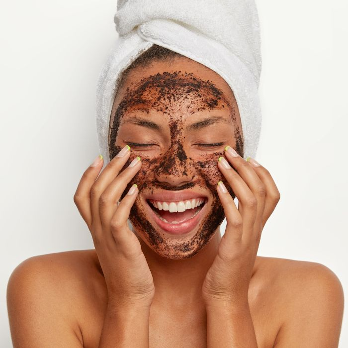 coffee grinds mask on womans face with white towel on her head homemade face mask white background
