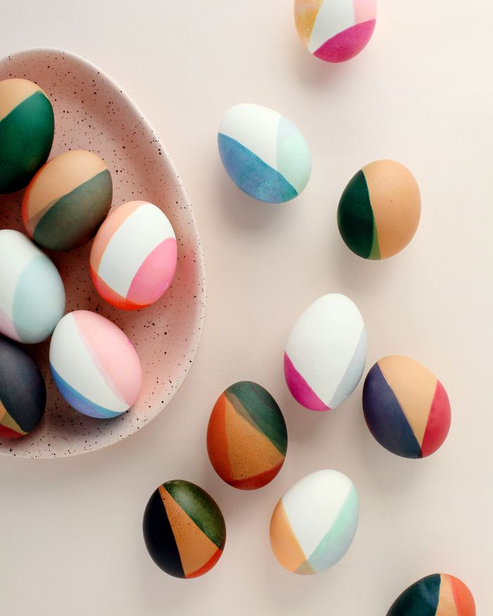 color blocked eggs in different colors easter egg coloring scattered around egg shaped plate on white surface