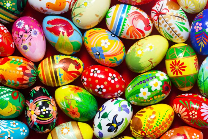 colorful eggs with different patterns and drawings on them dying easter eggs scattered on red surface