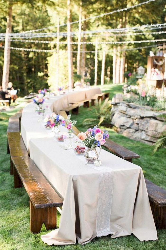 colorful flower bouquets on long table with white cloth on it backyard wedding decorations vintage benches around it