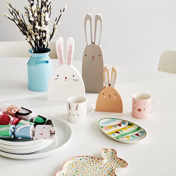 cute bunnies made from carton next to mugs outdoor easter decorations placed on white table