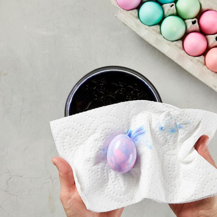 decorated egg being dried with a paper towel how to dye eggs with food coloring step by step diy tutorial