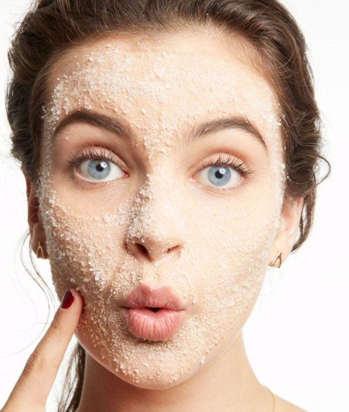 diy face mask for acne blue eyed woman with brown hair putting on exfoliating mask on her face