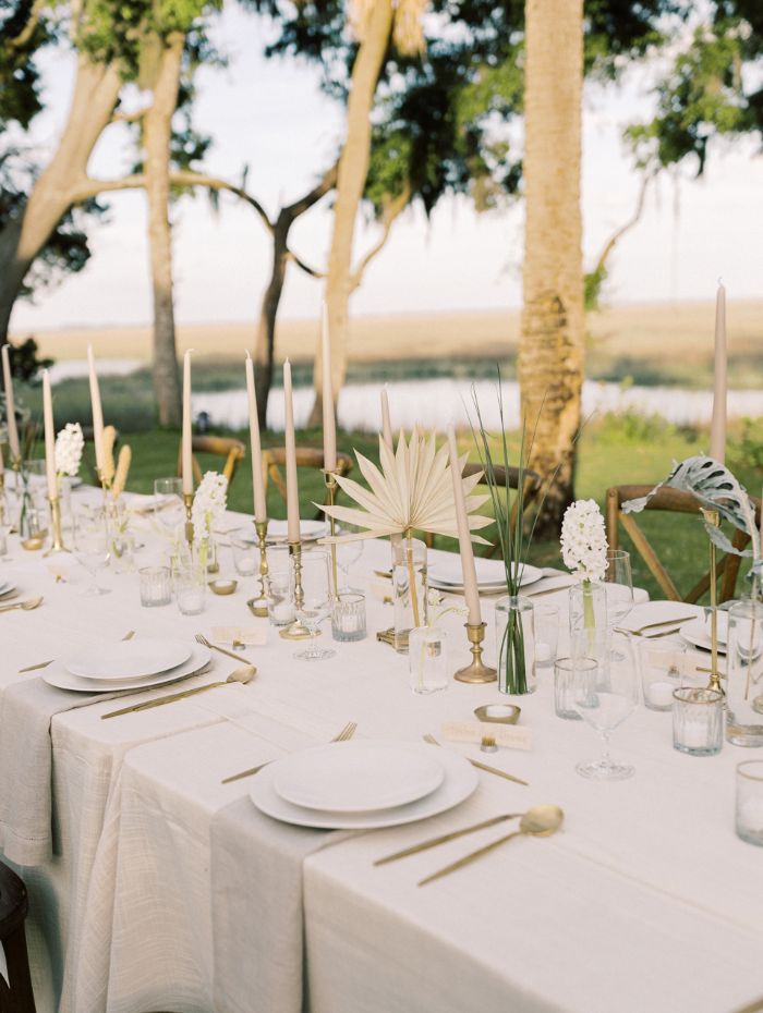 dried flower bouquets on long table with white cloth outdoor wedding decorations tall trees in the background