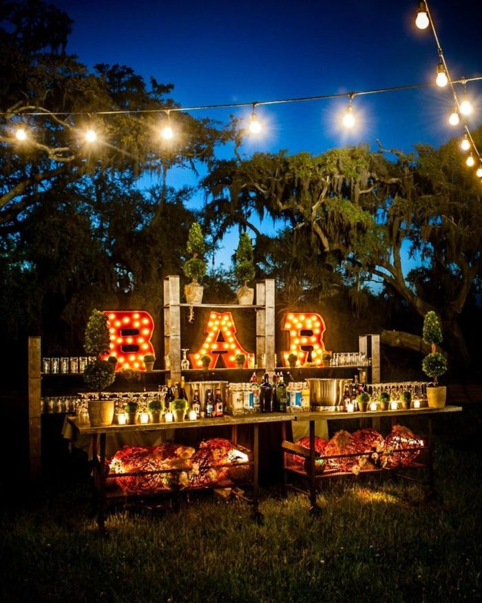 drinks bar outside with wood tables sign with lights backyard wedding strings of lights hanging above