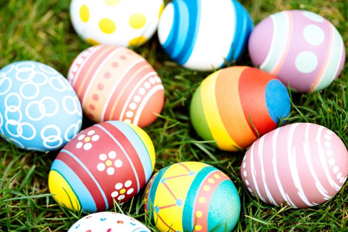 dying easter eggs colorful eggs scattered around grass field in blue pink red yellow with different patterns