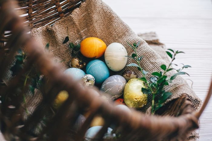dying eggs with food coloring eggs in yellow blue gray and gold inside wooden basket with burlap cloth