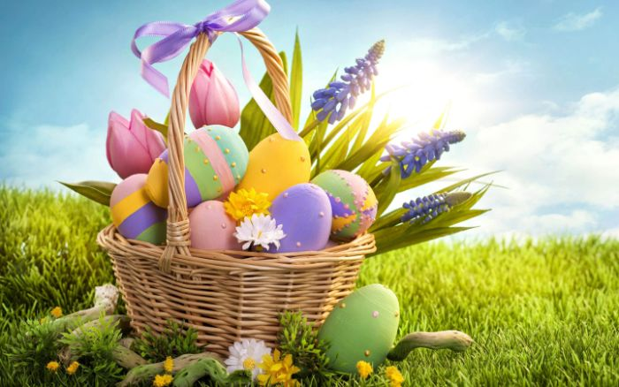 easter background basket filled with easter eggs in different colors and patterns and flowers