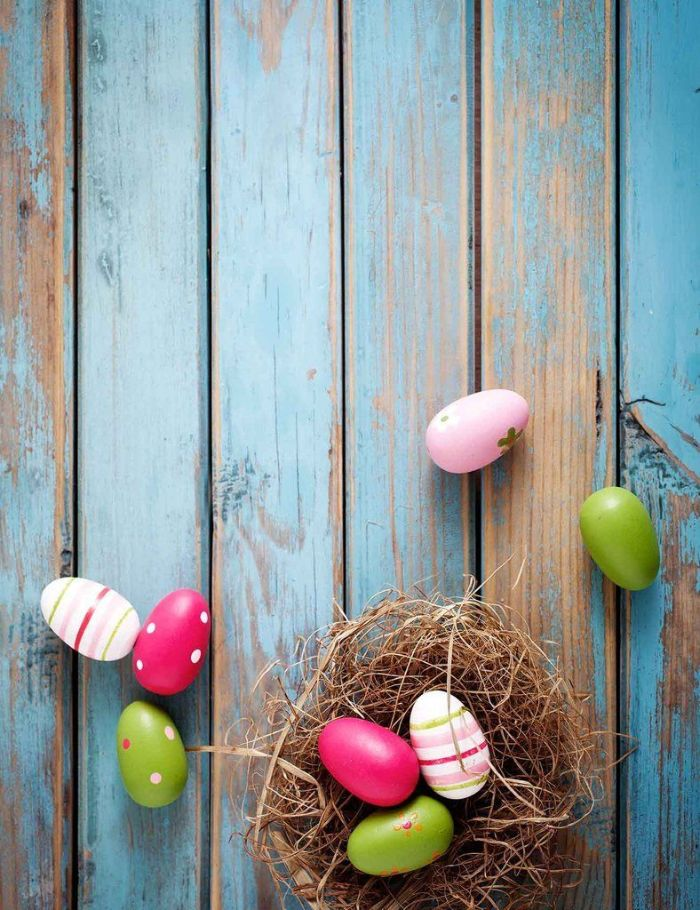 easter background free nest with eggs in different colors placed on blue wooden surface