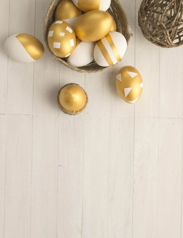 easter background images eggs dyed in gold and white placed in wicker basket on white wooden surface