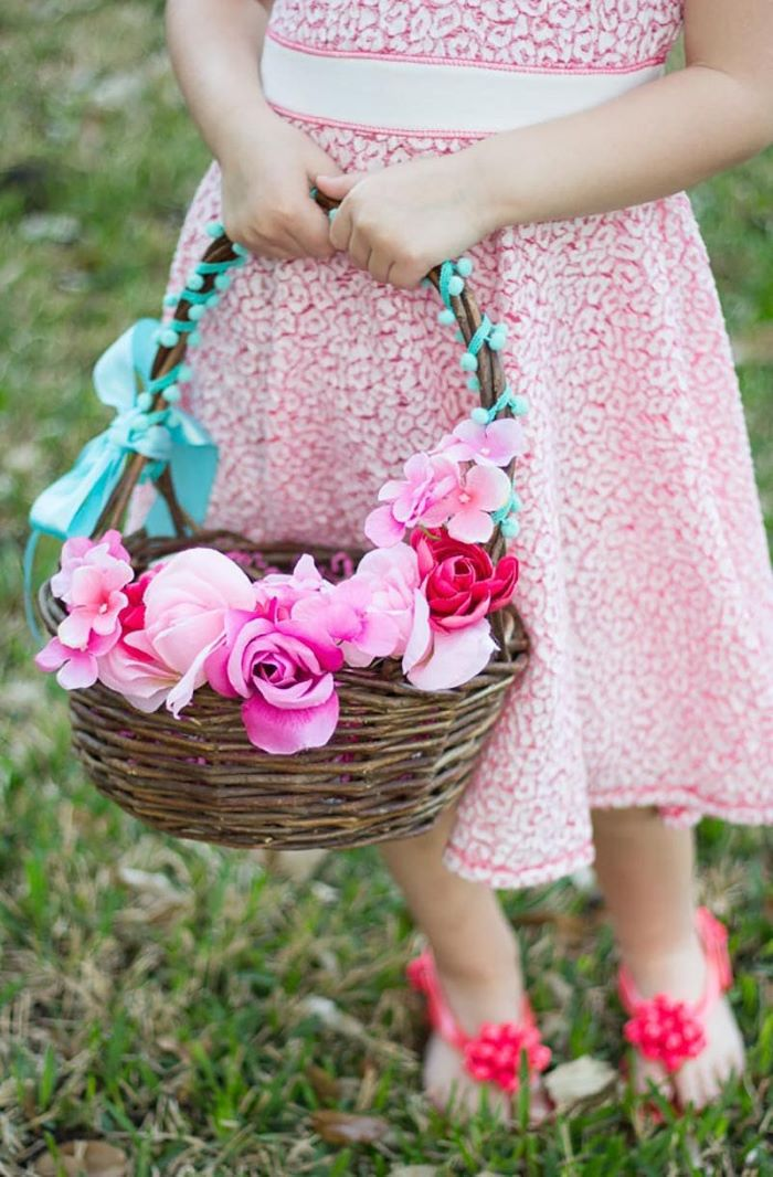 easter basket ideas for toddlers girl wearing blue and red lace dress holding basket with flowers