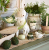 easter decorations ceramic bunny placed in the middle surrounded flowers in ceramic pots