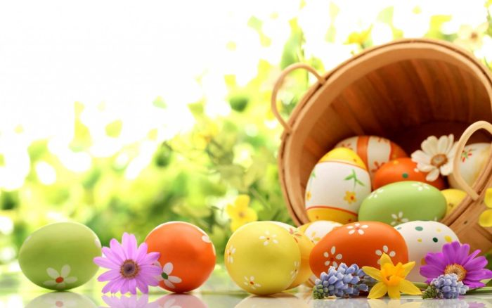 easter egg background wooden basket filled with eggs in yellow orange and green with floral decorations