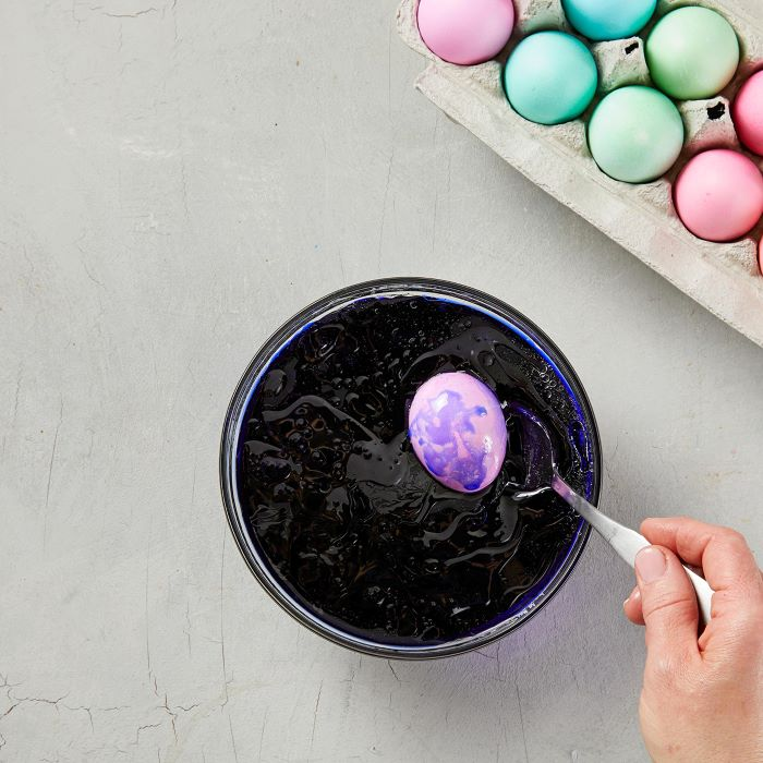 egg being dipped in bowl filled with dye and oil how to dye eggs with food coloring stirred with a spoon