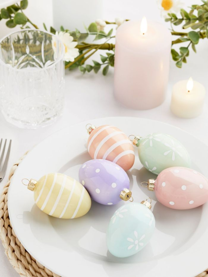egg shaped baubles in different colors placed inside white plate diy easter decorations greenery table runner